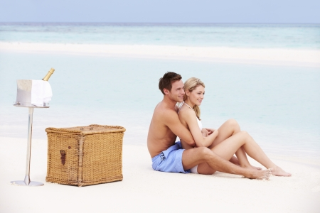 Couple On Beach With Luxury Champagne Picnic photo