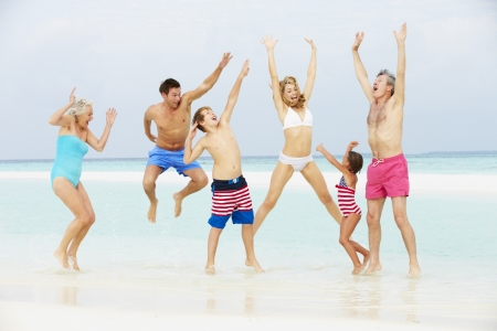 Multi Generation Family Having Fun In Sea On Beach Holiday