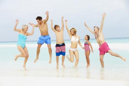 Multi Generation Family Having Fun In Sea On Beach Holiday Stock Photo - 19530194