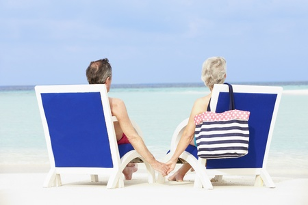 Senior Couple On Beach Relaxing In Chairs photo