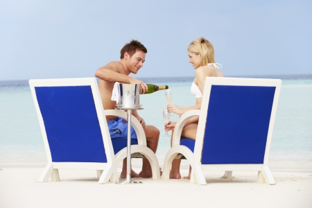 Couple On Beach Relaxing In Chairs And Drinking Champagne photo
