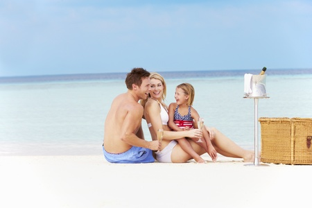 Family On Beach With Luxury Champagne Picnic photo