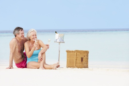 Senior Couple On Beach With Luxury Champagne Picnic photo