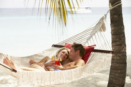 honeymoon couple: Romantic Couple Relaxing In Beach Hammock Stock Photo