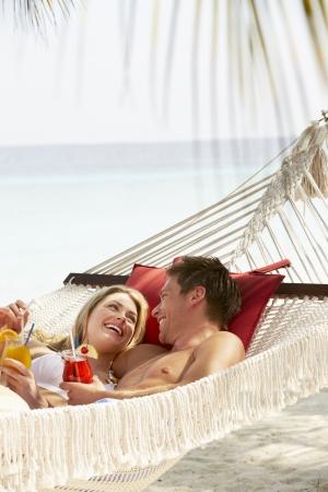 in hammock: Romantic Couple Relaxing In Beach Hammock Stock Photo