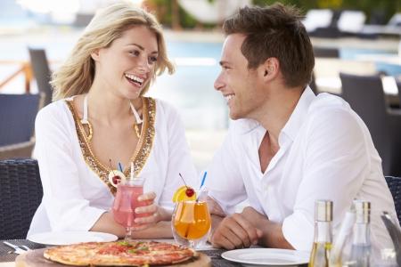pareja comiendo: Pareja disfruta de la comida en el exterior del restaurante