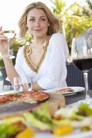 eating pizza: Woman Enjoying Meal In Outdoor Restaurant Stock Photo