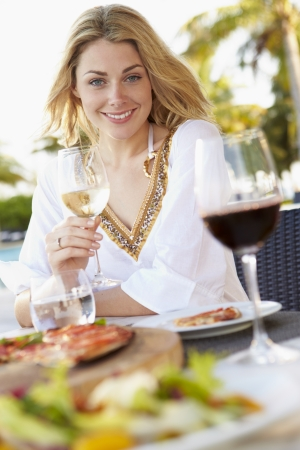 glass of white wine: Woman Enjoying Meal In Outdoor Restaurant Stock Photo
