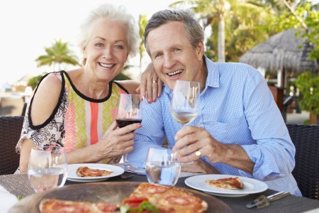 eating pizza: Senior Couple Enjoying Meal In Outdoor Restaurant