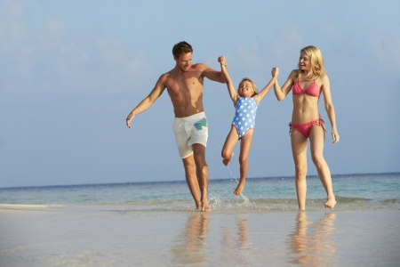 Family Having Fun In Sea On Beach Holiday photo