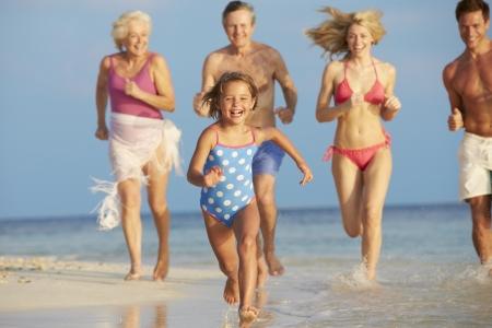 abuelos: Multi generacional que se divierten en el mar en la playa de vacaciones