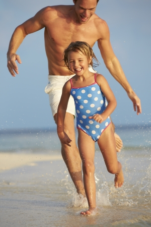 Father And Daughter Having Fun In Sea On Beach Holiday photo