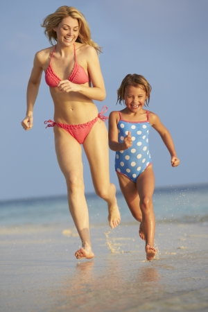 Mother And Daughter Having Fun In Sea On Beach Holiday photo