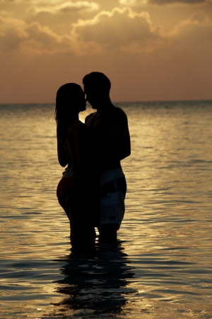 Silhouette Of Romantic Couple Standing In Sea photo