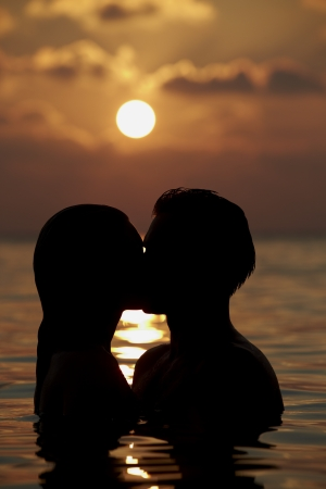 hugging couple: Silhouette Of Romantic Couple Standing In Sea