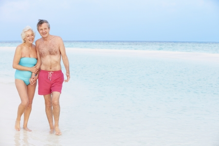 Senior Romantic Couple Walking In Beautiful Tropical Sea photo