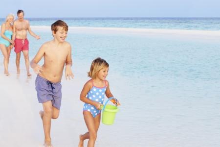 5 10 year old girl: Grandparents And Grandchildren Having Fun On Beach Holiday Stock Photo