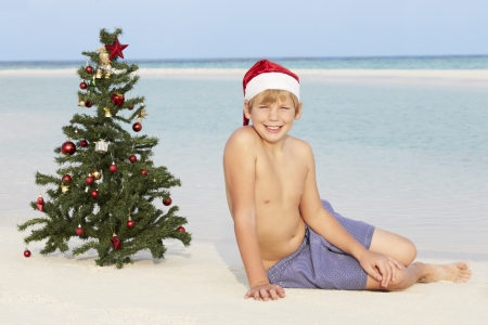 Boy Sitting On Beach With Christmas Tree And Hat photo