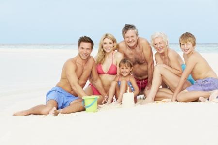 Grandparents And Grandchildren Having Fun On Beach Holiday Фото со стока