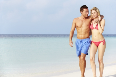 Romantic Couple Walking On Beautiful Tropical Beach photo