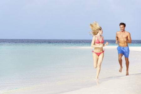 Romantic Couple Running On Beautiful Tropical Beach photo