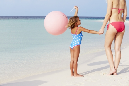 Mother And Daughter Running On Beautiful Beach With Balloon photo