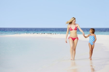 Mother And Daughter Walking On Beautiful Beach photo