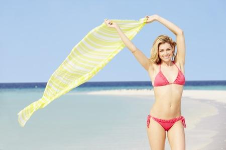 Woman In Bikini On Beautiful Tropical Beach Holding Sarong photo