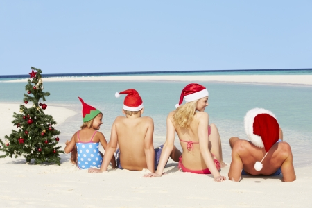 5 10 year old girl: Family Sitting On Beach With Christmas Tree And Hats