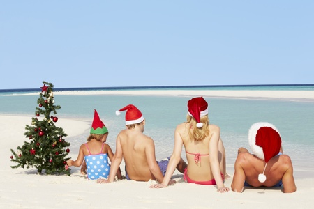 tropical christmas: Family Sitting On Beach With Christmas Tree And Hats