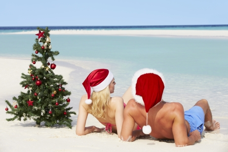 Couple Sitting On Beach With Christmas Tree And Hats Stock Photo