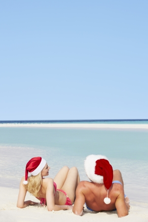 Couple Sitting On Beach Wearing Santa Hats photo
