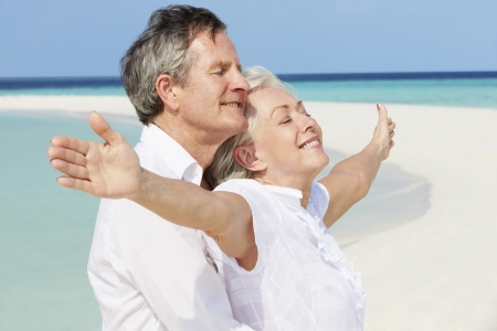 freedom couple: Senior Couple Withs Arms Outstretched On Beautiful Beach