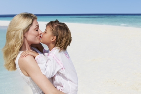 women kissing: Mother And Daughter Hugging On Beautiful Beach