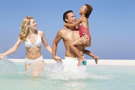 child in bikini: Family Having Fun In Sea On Beach Holiday