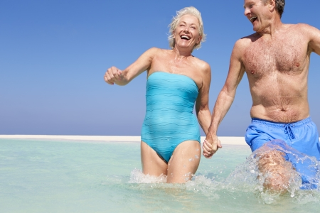 Senior Couple Having Fun In Sea On Beach Holiday photo