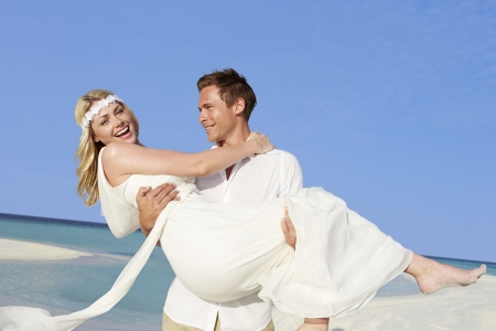Groom Carrying Bride At Beautiful Beach Wedding photo