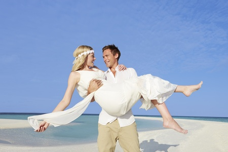 lift and carry: Groom Carrying Bride At Beautiful Beach Wedding