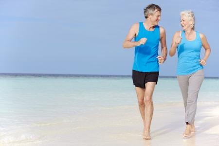 hacer footing: Pares mayores que se ejecutan en la playa hermosa