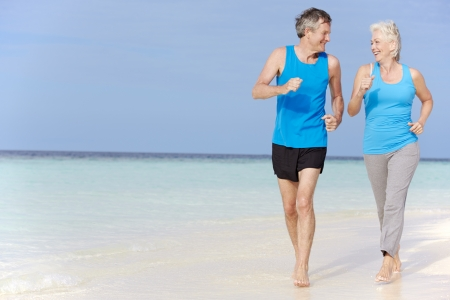 active: Senior Couple Running On Beautiful Beach