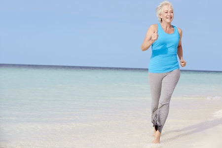 healthy seniors: Senior Woman Running On Beautiful Beach Stock Photo