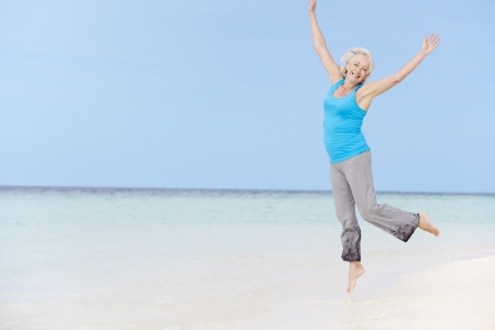 Senior Woman Jumping On Beautiful Beach photo