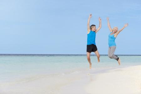 hombres haciendo ejercicio: Pares mayores que saltan en Hermosa Beach
