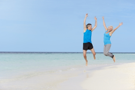senior exercising: Senior Couple Jumping On Beautiful Beach