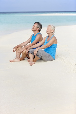 Senior Couple In Sports Clothing Relaxing On Beautiful Beach photo