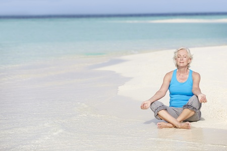 Senior Woman Meditating On Beautiful Beach photo