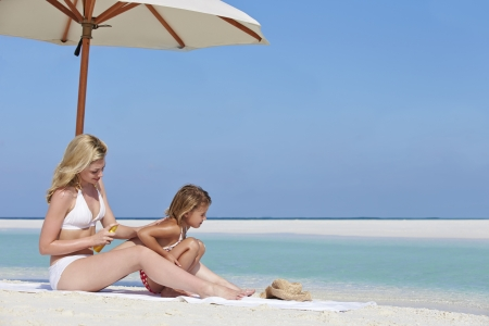 Mother Protecting Daughter With Sun Lotion On Beach Holiday photo