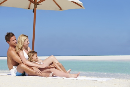 Family Sitting Under Umbrella On Beach Holiday photo
