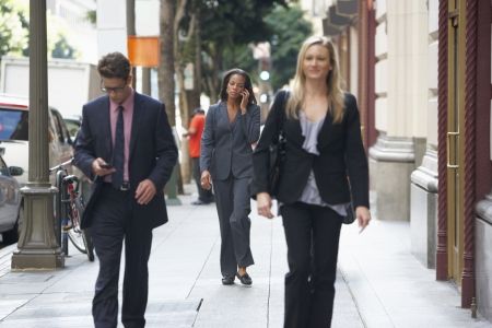 Group Of Businesspeople Walking Along Street photo