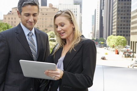 Businessman And Businesswoman Using Digital Tablet Outside photo
